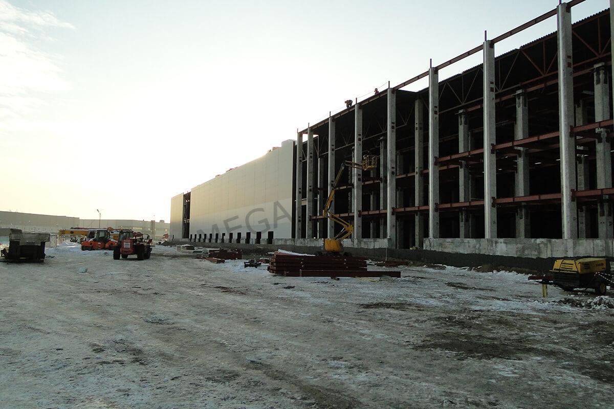 рабочие проводят работы по возведению промышленного здания